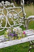 Posy of wild flowers on garden bench
