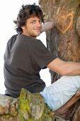 Lächelnder Mann ritzt ein Herz in einen Baumstamm