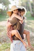 Lächelndes Paar umarmt sich auf der Wiese