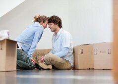 Paar mit Umzugskartons in der Wohnung
