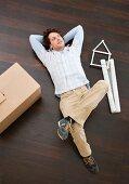 Mann liegt zwischen Umzugskarton, Planrolle und Hausmodell am Boden