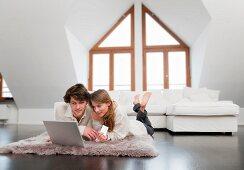Pärchen beim Online-Shopping im Wohnzimmer