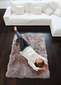 Frau liegt auf dem Wohnzimmerteppich