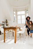Mother, daughter and dog running through a kitchen