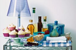 Desserts on cake stand in front of table lamp with blue lampshade and various kitchen utensils