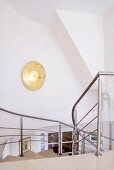 Golden wall lamp on stairwell wall and view down staircase with stainless steel balustrade
