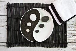 Yin and Yang dish with black pumice and white pebbles on bamboo mat