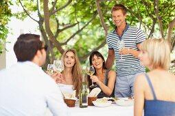 Friends drinking wine in a garden