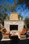 Outdoor sitting area with sofas near stone fireplace