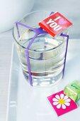 Schoko-Grüsse und ein Glas Wasser mit lila Gummiband