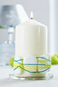 White pillar candle decorated with pebbles and rubber bands