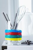 Glass container of kitchen utensils used as holder for rubber bands