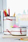 Mit Papier und Gummibändern verzierte Konservendosen als Stifthalter