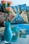 Turquoise vase of flowers on glass table in front of couch with Oriental upholstery and scatter cushions