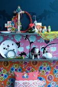 Souvenirs, plates and small teapot on shelves backed with different wallpapers