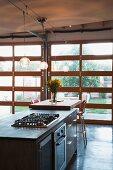 Moderner Küchenblock vor Terrassentür mit Gartenblick