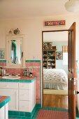 Rustic bathroom with open door and view of bed in bedroom beyond