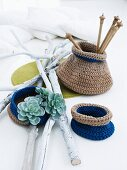 Small, two-tone, crocheted bags for nick-nacks arranged with white-painted twigs and succulent plants