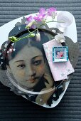 Place setting with delicate orchid spray in beaker on white china plate and metal plate with portrait of Japanese woman