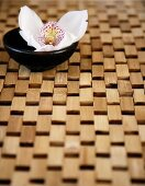 An orchid flower in a little black bowl on a bamboo-wood mat