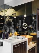 Dark, reflective glass surfaces with floral pattern behind washstand with wooden doors and yellow basin
