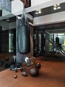Elegant home gym with punchbag against floral patterned wall and dark mirrors