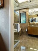 View through an open door into a modern bathroom with light brown flooring and wall tiles