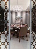 Elegant dining room with chandelier and printed wall paper