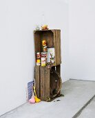 Tins of food in stack of vintage wooden crates and colourful, retro, plastic ladles leaning on wall