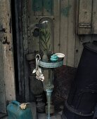 Vintage metal plant stand next to old round iron stove against grey board wall