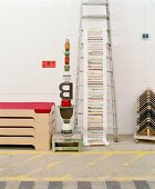 Stacked containers and decorative goods on rustic wooden footstool next to modern bed and ladder with printed paper banner leaning on wall