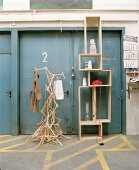 Artistic coat rack made of coathangers next to modern wooden shelving in front of grey metal doors