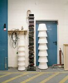 Stacked white lampshades in front of metal door next to modern bookcase