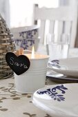 Lit tealight in metal bucket with heart-shaped, blackboard place name on set table