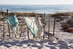 Cloths printed with map motifs tied to old wooden posts and fluttering in the wind next to wooden walkway leading through dunes to sea