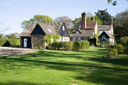 Old, English property with large lawns and hedges in front of various parts of building in summer atmosphere