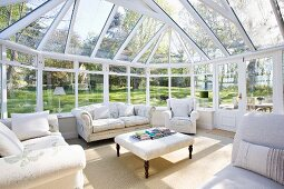 Spacious conservatory in extensive gardens; pale, traditional sofas and armchairs grouped around ottoman