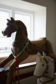 Large, antique rocking horse with artistic carved detail and smaller stuffed fabric horse in front of window