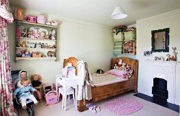 Solid wood bed, open fireplace and arranged dolls and soft toys in corner of child's bedroom with nostalgic ambiance