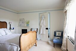 Antique double bed with high, wooden headboard and footer, patterned, pale blue chaise longue and curtains with pelmet in bright, nostalgic bedroom