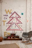 Bauhaus rocking chair in front of Christmas tree sketched on wall in rustic interior