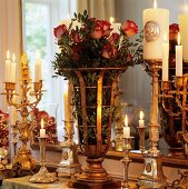 Bouquet of roses in brass vase surrounded by silver candlesticks with lit candles in front of mirror