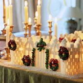An illuminated house made from sugar cubes, on a table in front of candle holders with lit candles