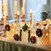 Beleuchtetes Häuschen aus Zuckerwürfeln vor Kerzenständer mit brennenden Kerzen auf Tisch