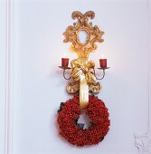 Gilt wall bracket with lit candles and wreath of red berries on white wooden wall