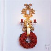 Vergoldete Wandkonsole mit brennenden Kerzen und Kranz aus roten Beeren an weisser Holzwand