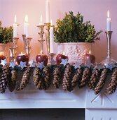 Festlich dekorierter Kaminsims mit Tannenzapfen und Kerzenständern mit brennenden Kerzen