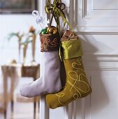 Baubles and presents in colourful Christmas stockings hanging on door handle of white interior door