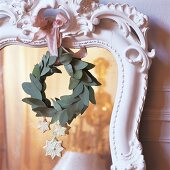Christmas decorations and wreath of leaves hanging on mirror with ornate, white wooden frame