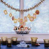 Weihnachtsplätzchen auf Girlande gehängt über Dekoschale am Fenster